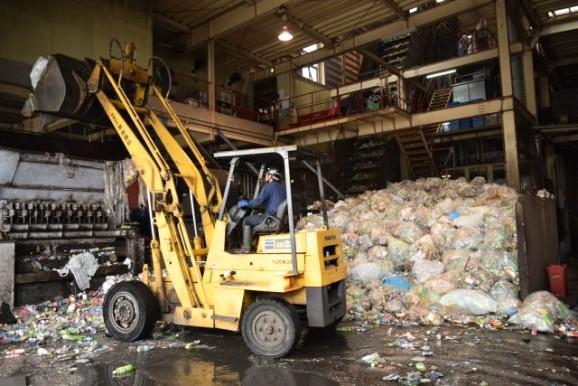 (投入した袋を破く機械に通し、ビニール袋、古紙、大きな金属など容器以外のものを省く。)
